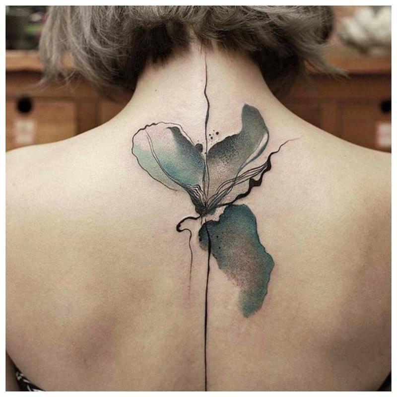 Акварельная тату в виде цветка между лопаток