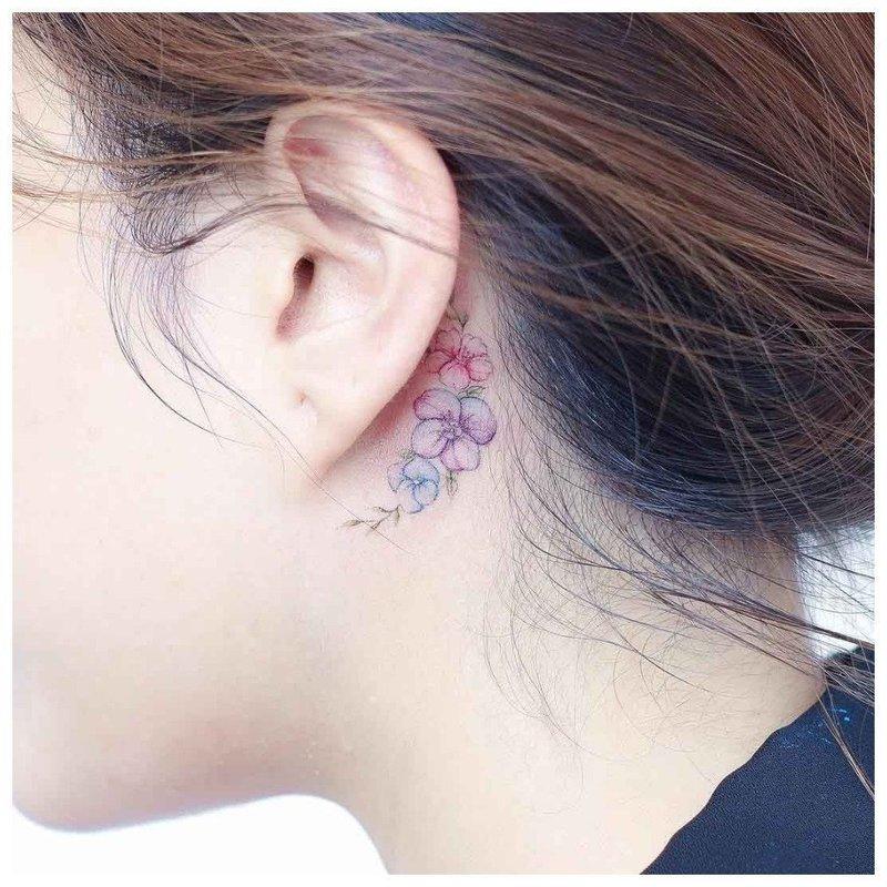 Нежный цветок тату на шее у девушки
