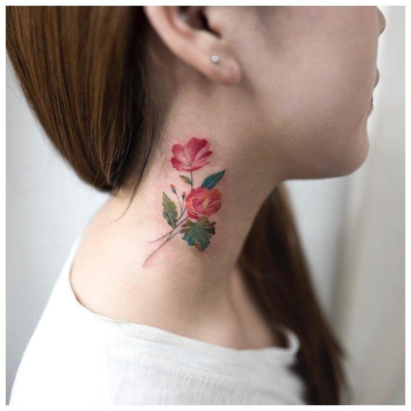 Яркий цветок на шее у девушки - тату
