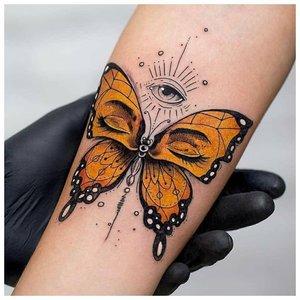 Яркая бабочка на руке у девушки