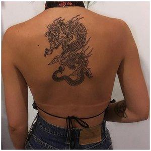 Тату дракона на спине у женщины
