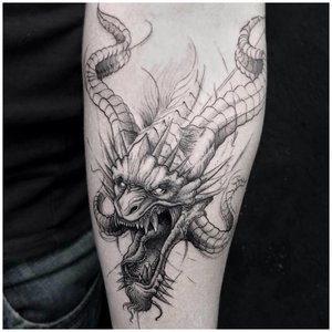 Тату дракона на руке у мужчины