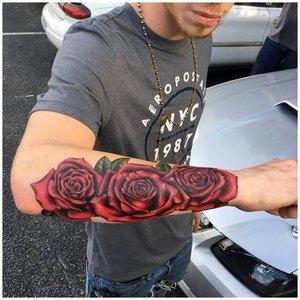Три красные розы тату на руке у мужчины