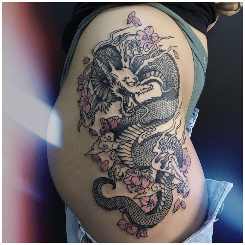 Тату дракона у девушки на бедре