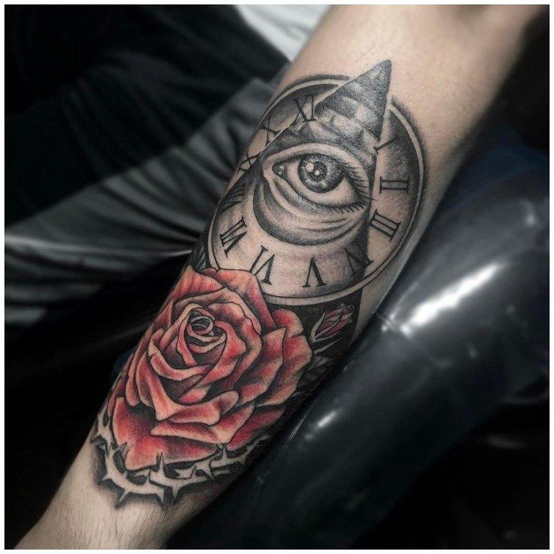 Тату роза и всевидящее око на руке у мужчины