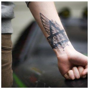 Тату на запястье с треугольником и крыльями