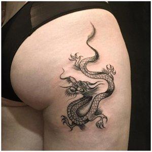 Тату дракона на задней поверхности бедра у девушки