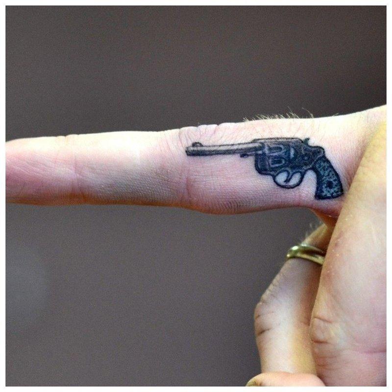 Тату револьвера на ребре пальца