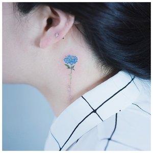 Тату на шее с голубым цветком