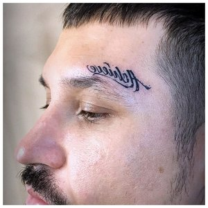 Татуировка надпись над бровью