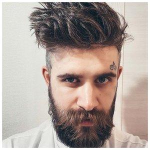 Мужчина с бородой и тату под бровью