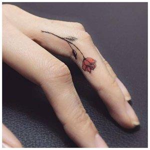 Татуировка в виде розы на пальце руки