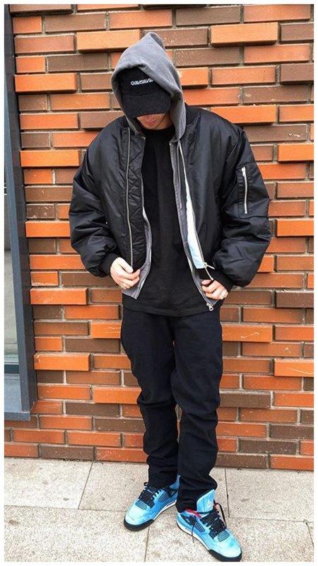 Олег Майами в куртке позирует у стены
