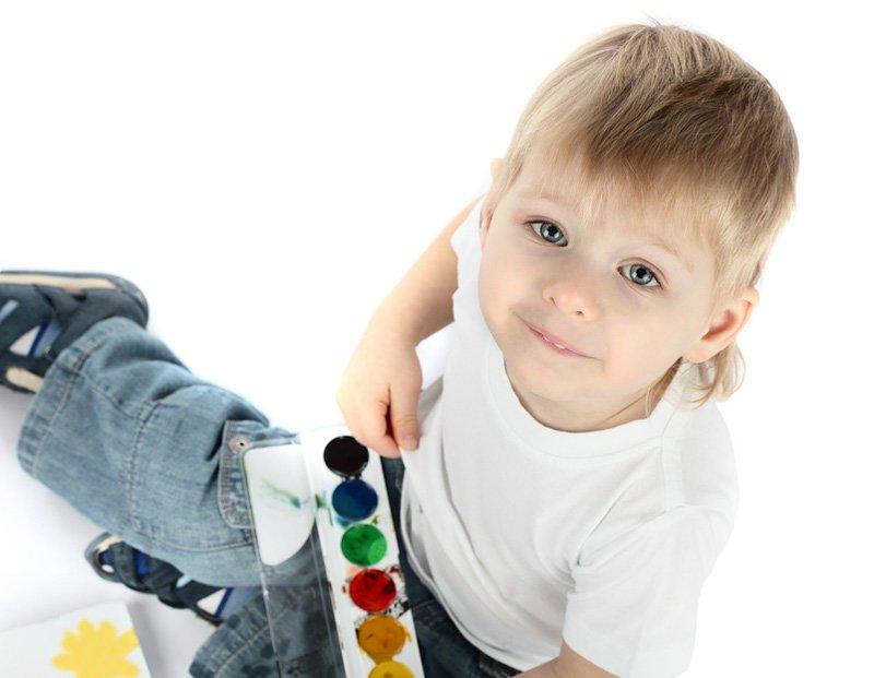Мальчик играет с красками